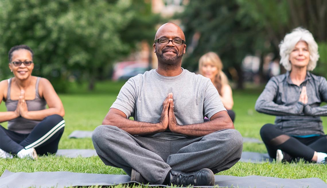 A multi-ethnic group of seniors is attending a yoga class outdoors