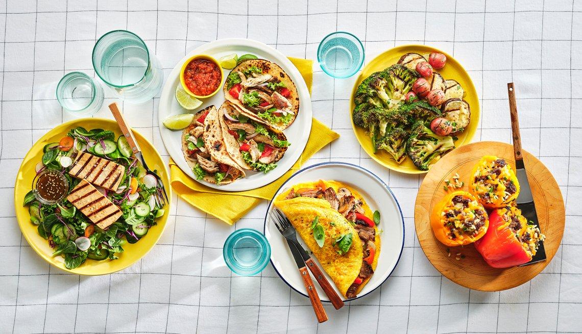 Platos de comida que incluyen tofu a la parrilla tacos de pollo borracho hamburguesa pimientos rellenos y paleta de cerdo