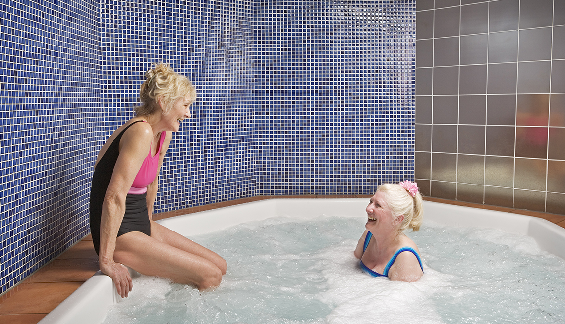 woman sitting in a hot tub and talking to another woman sitting on the side of the hot tub