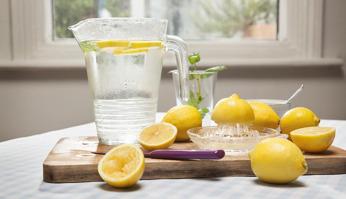 Limones enteros y cortados y una jarra de agua con rebanadas de limón