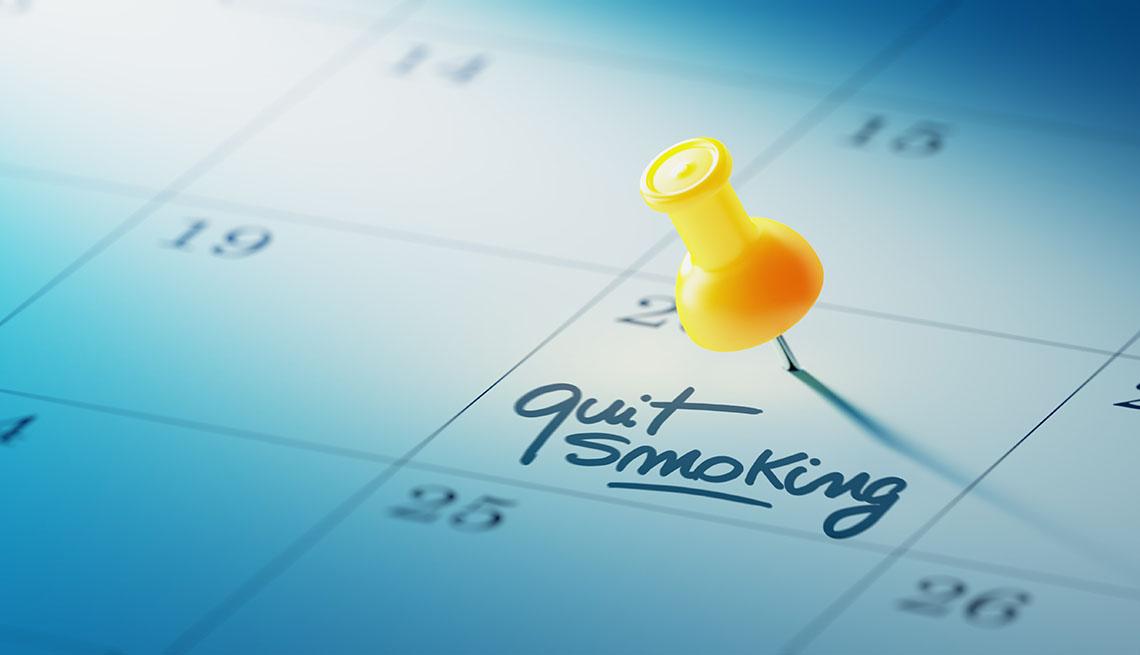 Un calendario con una tachuela que marca un día que dice dejar de fumar en inglés