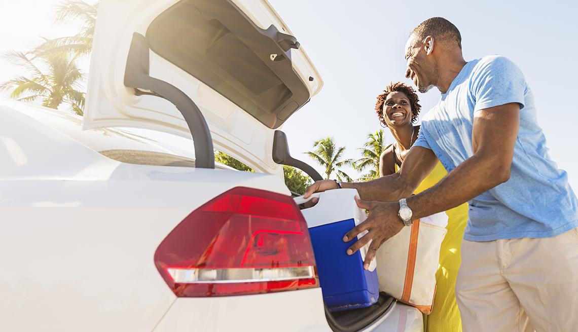 Una pareja acomoda una nevera portatil y bultos en el baúl de su auto