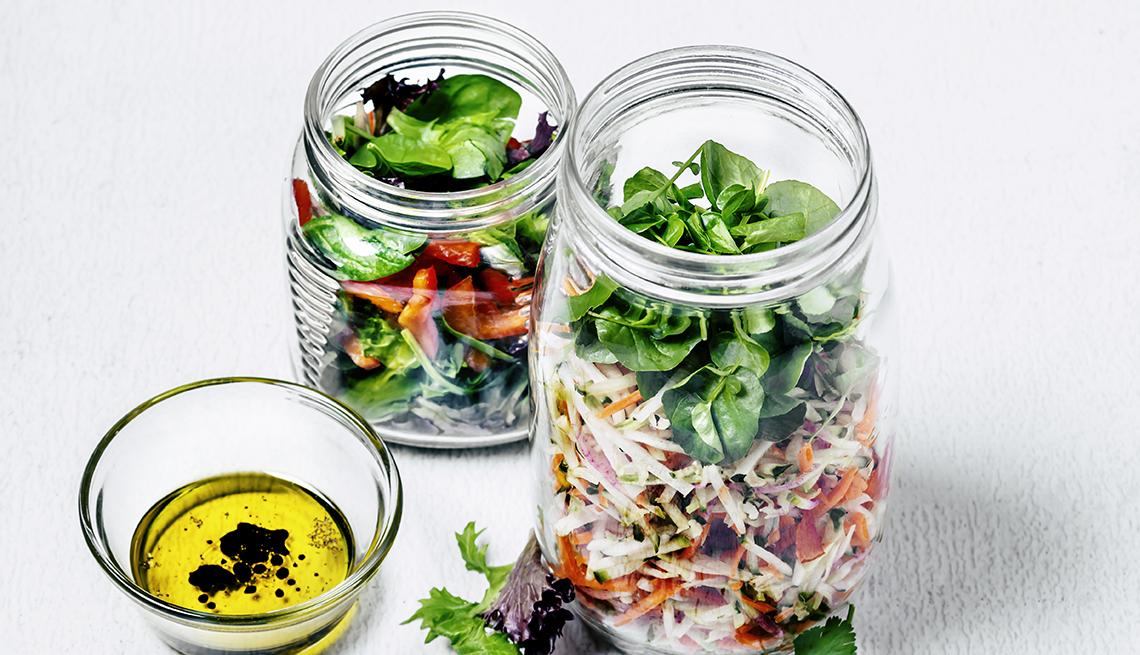 Dos jarras con ensalada y un envase con aderezo de vinagre y aceite