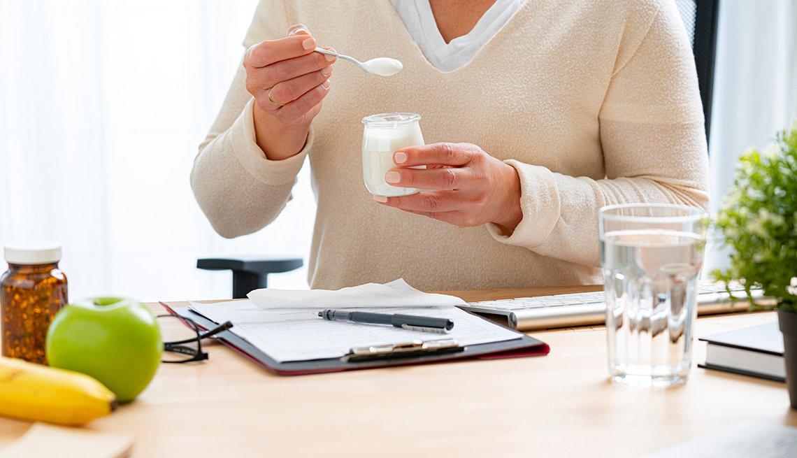 Una mujer come un yogur sentada en su escritorio