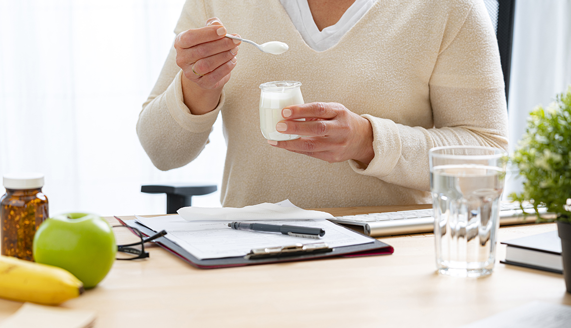 woman at her desk eating yogurt and drinking water, fruit and vitamins are nearby.