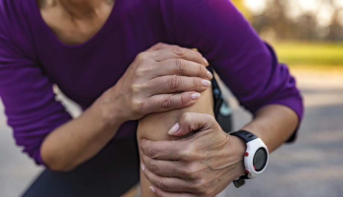 Una mujer abraza su rodilla en señal de dolor