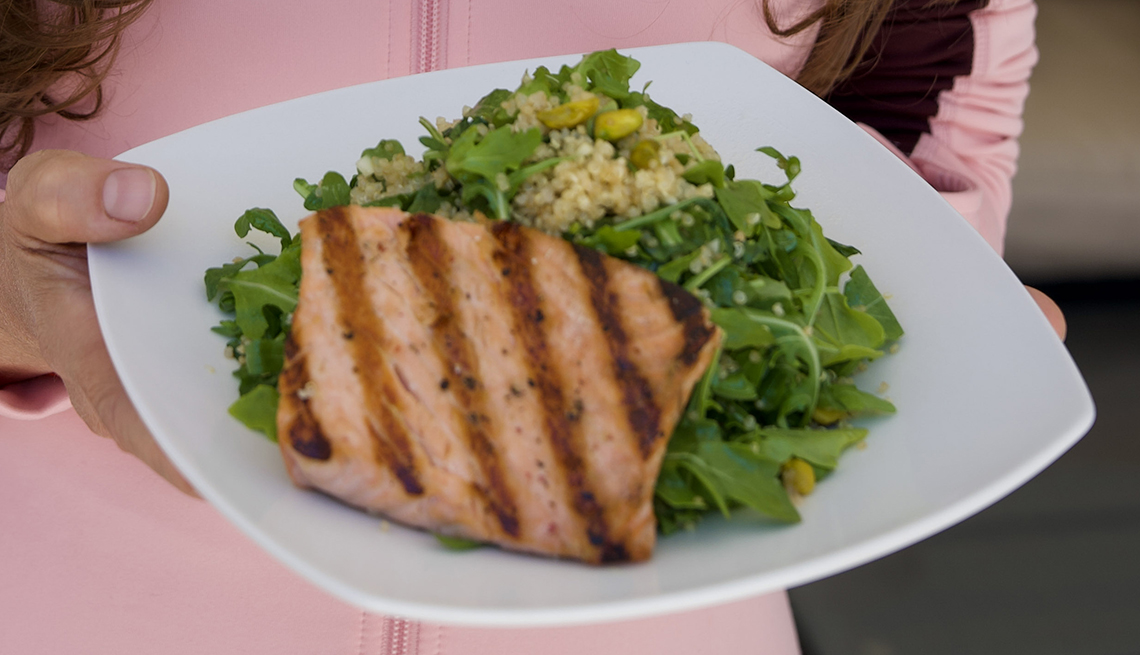 devin alexander holding a dish with her grilled salmon with pistachio and quinoa recipe