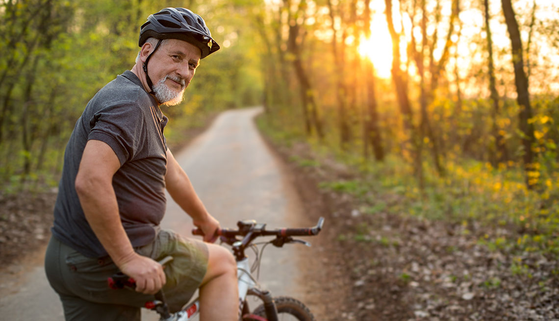 Un hombre corre bicicleta por un sendero