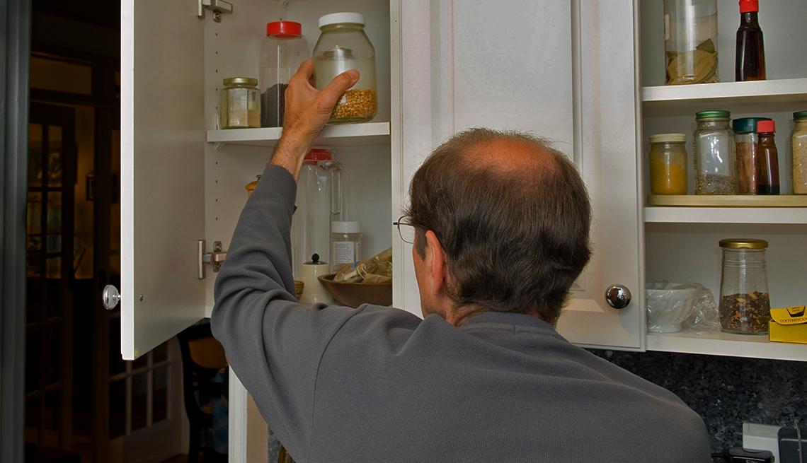 Hombre alcanza un frasco del gabinete en la cocina