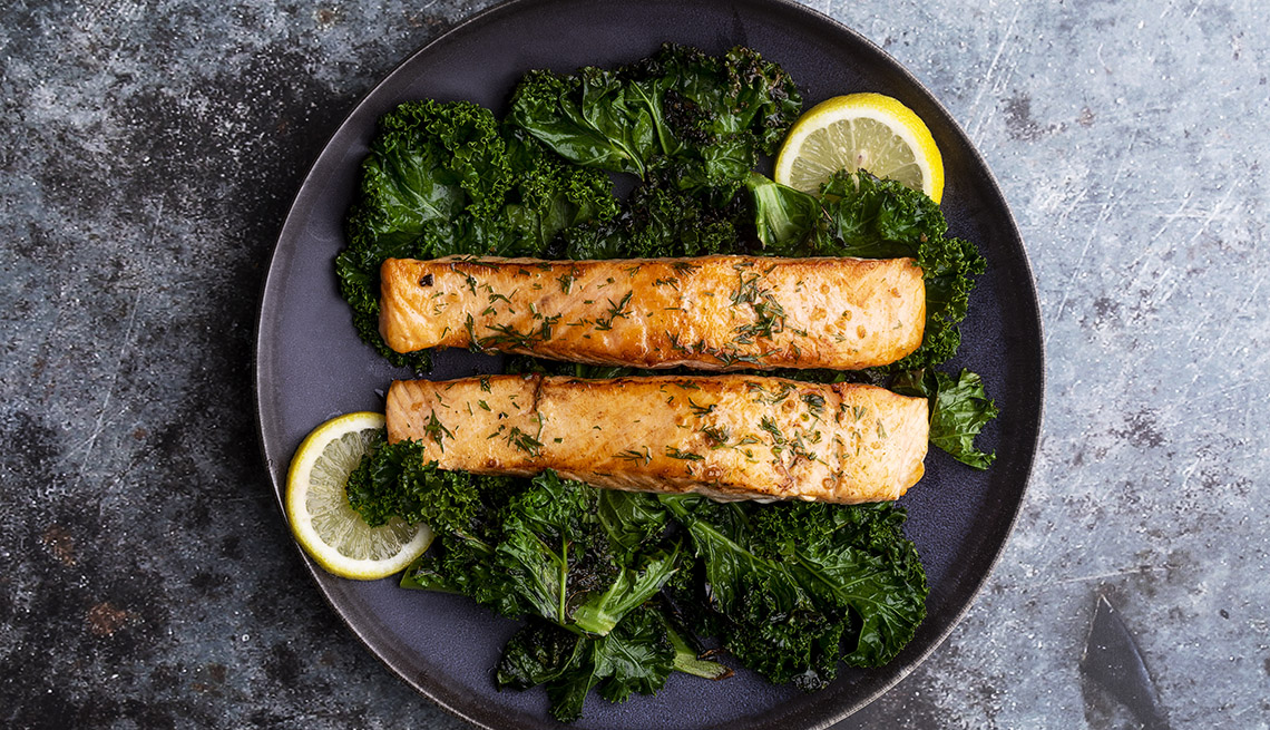 sautéed salmon fillets with kale, dill and lemon on a plate