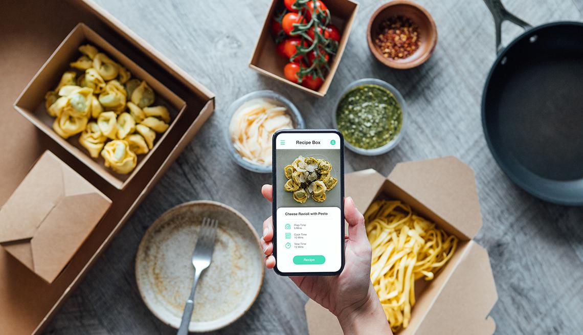 Vista de un teléfono inteligente e ingredientes sobre una mesa