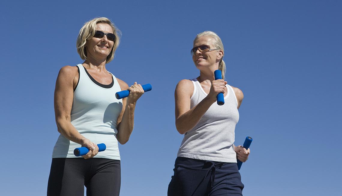 Dos amigas hacen una caminata con pesas