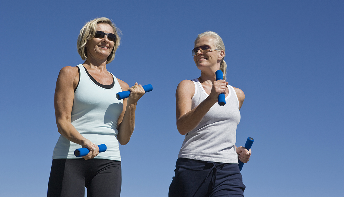 two women walking with weights in their hands