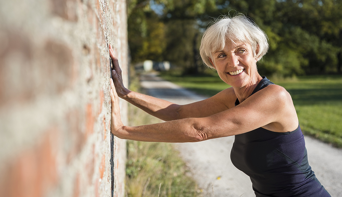 woman doing a pushup off of a brick wall outside