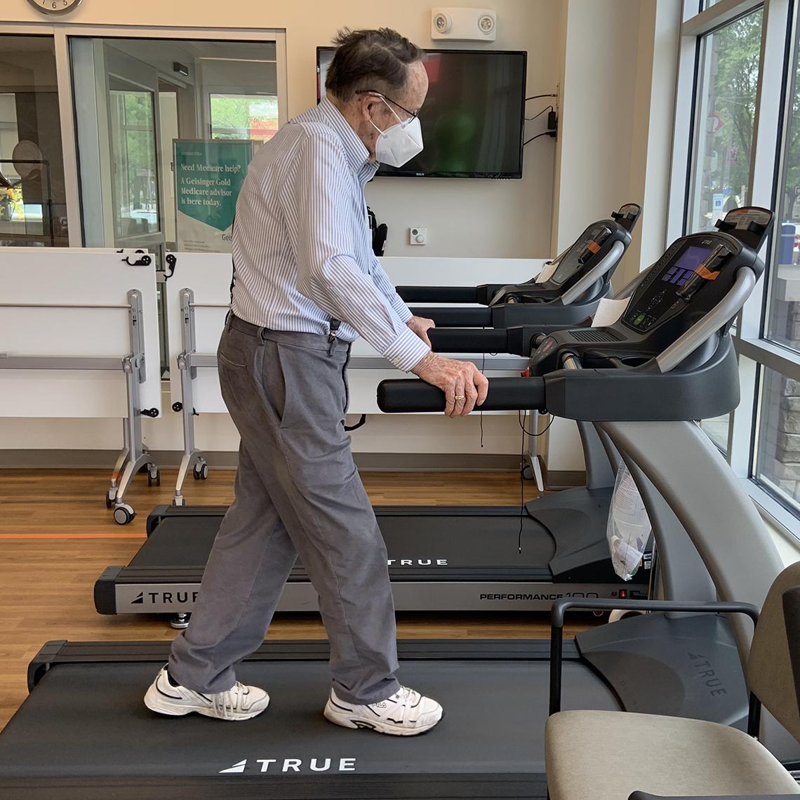 man using a treadmill, wearing a face mask