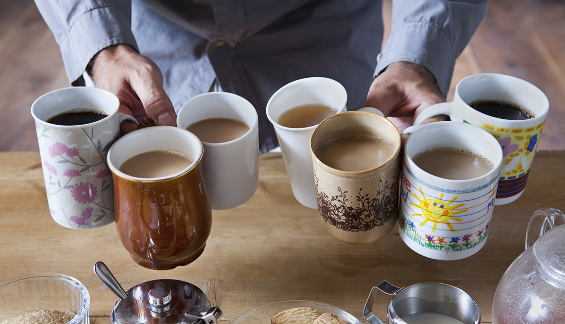 a person holding seven mugs of coffee by their handles in both hands