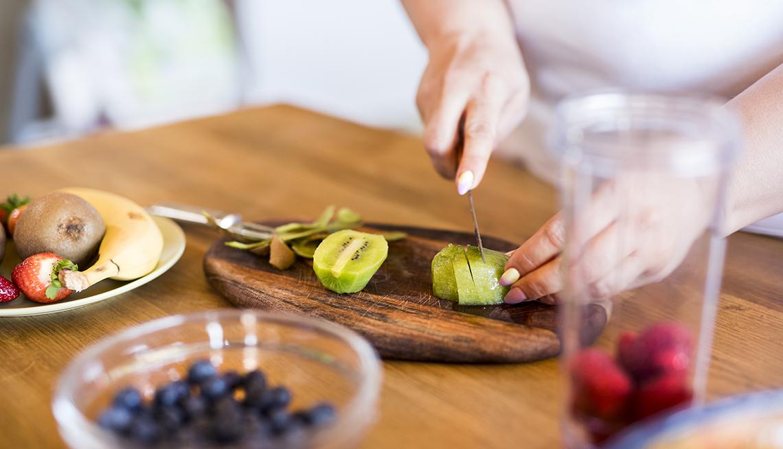 Una mujer corta un kiwi, también hay otros alimentos sobre la mesa