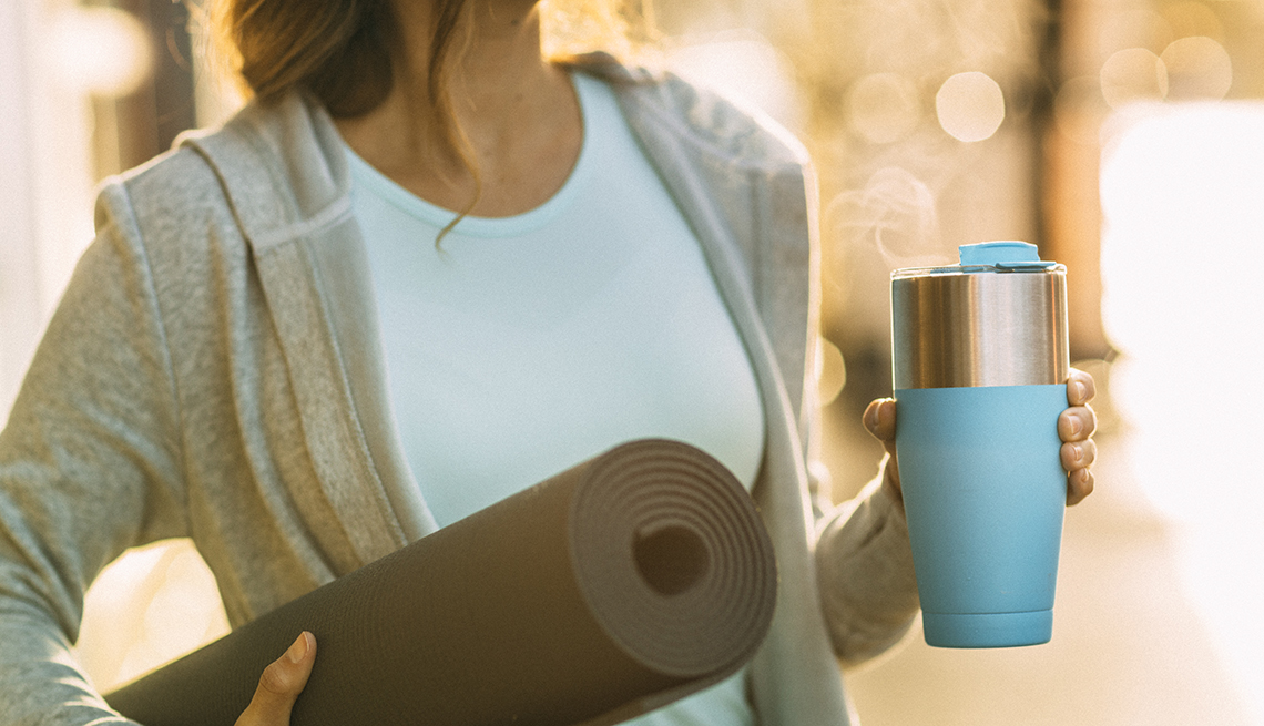 Healthy fit young woman headed to yoga with yoga mat and coffee cup