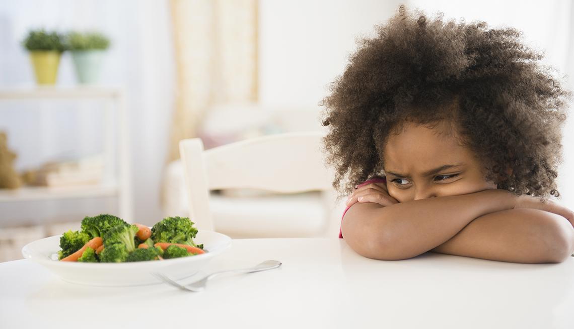 Una niña con sus brazos cruzados mira de reojo y molesta un plato de brócoli y zanahorias