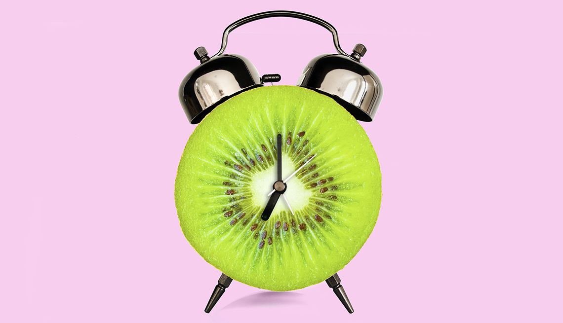an alarm clock made out of a sliced kiwi to symbolize foods for sleep