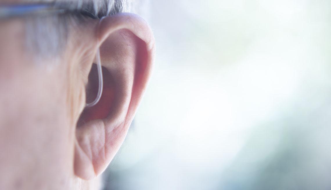 Foto de una oreja usando un audífono apenas perceptible