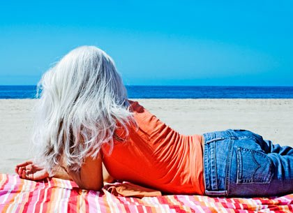 youthful middle aged woman on beach towel