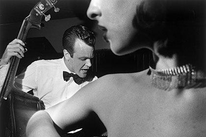 Hombre tocando un intrumento musical y una mujer oyendolo tocar - Escuchar música ayuda a dormir mejor en la noche.