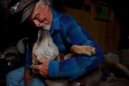 Hombre acariciando a su perro - Los dueños de perros son emocionalmente apegados a sus mascotas como a sus familiares más cercanos.
