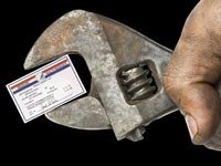 greasy hand holding an adjustable wrench with a Medicare card in its grip.