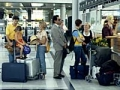 Travelers stand in line at airport