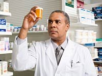 Pharmacist holds pill bottle, Medicare Part D Surcharge for Higher-Incomes