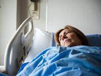 Paciente en cama de hospital mirando pensativamente por la ventana