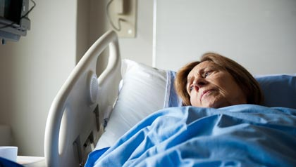 Patient in hospital bed looking pensively at the window, the cost of being labeled observed vs. admitted when at the hospital