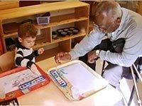 Niño dibujando con un adulto en una mesa - Vivir con Alzheimer - Pérdida de memoria y demencia