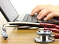 Médico escribiendo en su computadora y estetoscopio al lado