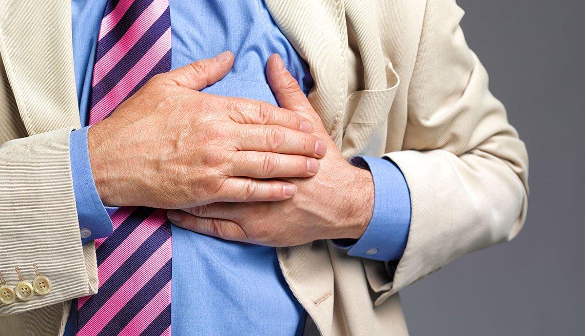 Hombre con sus manos en el pecho en señal de dolor