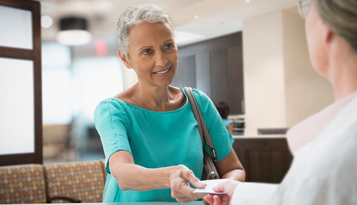 older woman receiving prescription from doctor