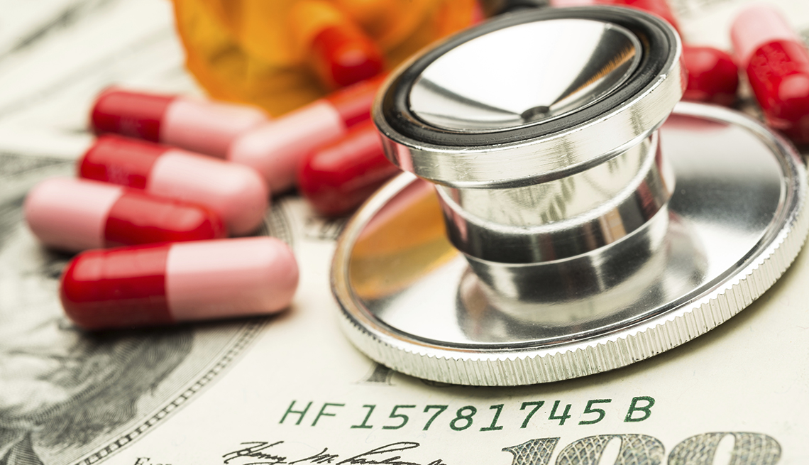 Estetoscopio plateado y píldoras rojas y rosadas encima de un billete de 100 dólares.