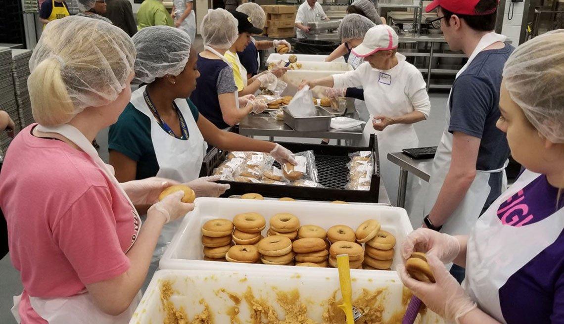 Voluntarios de MANNA preparan sándwiches con bagels integrales y hummus.