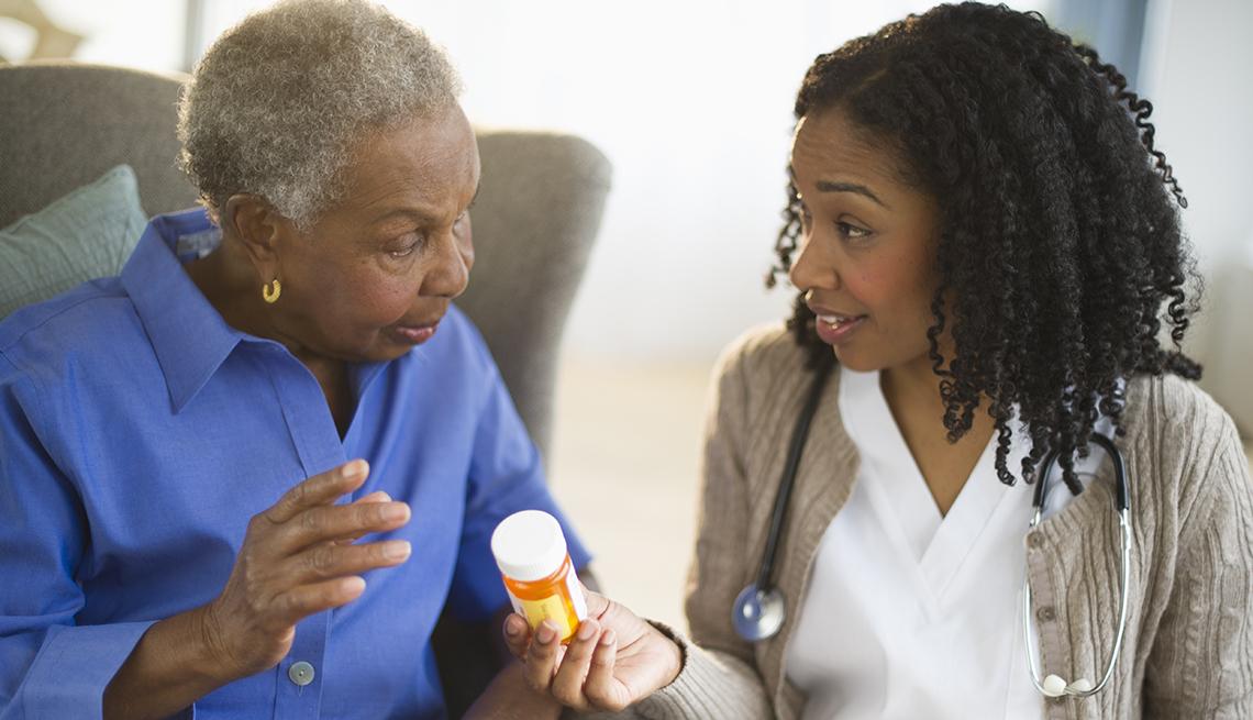 Mujer recibiendo un frasco de pastillas de una doctora