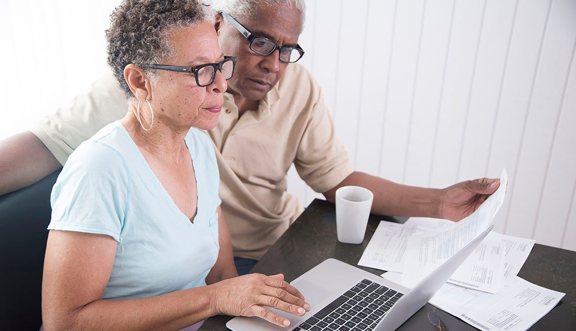 Mature couple sitting at table, using laptop, looking at paperwork.