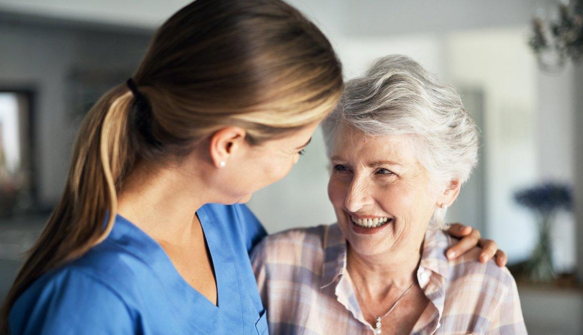 Enfermera abrazando a otra mujer