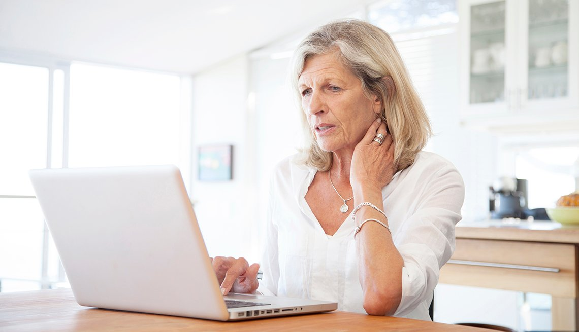 Mature women working on a laptop in a kitchen