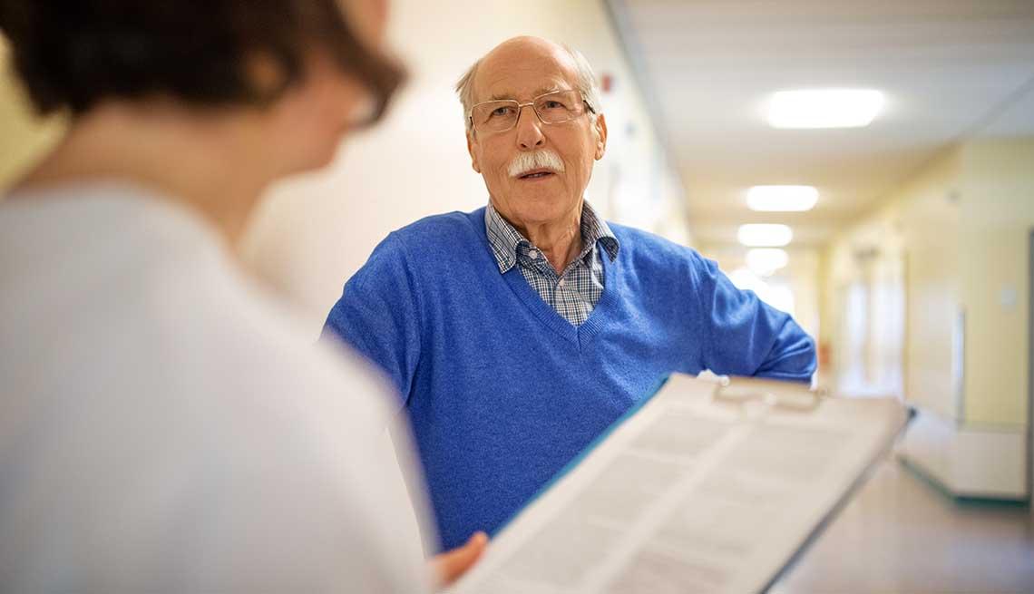 Senior man talking with doctor in hospital hallway.