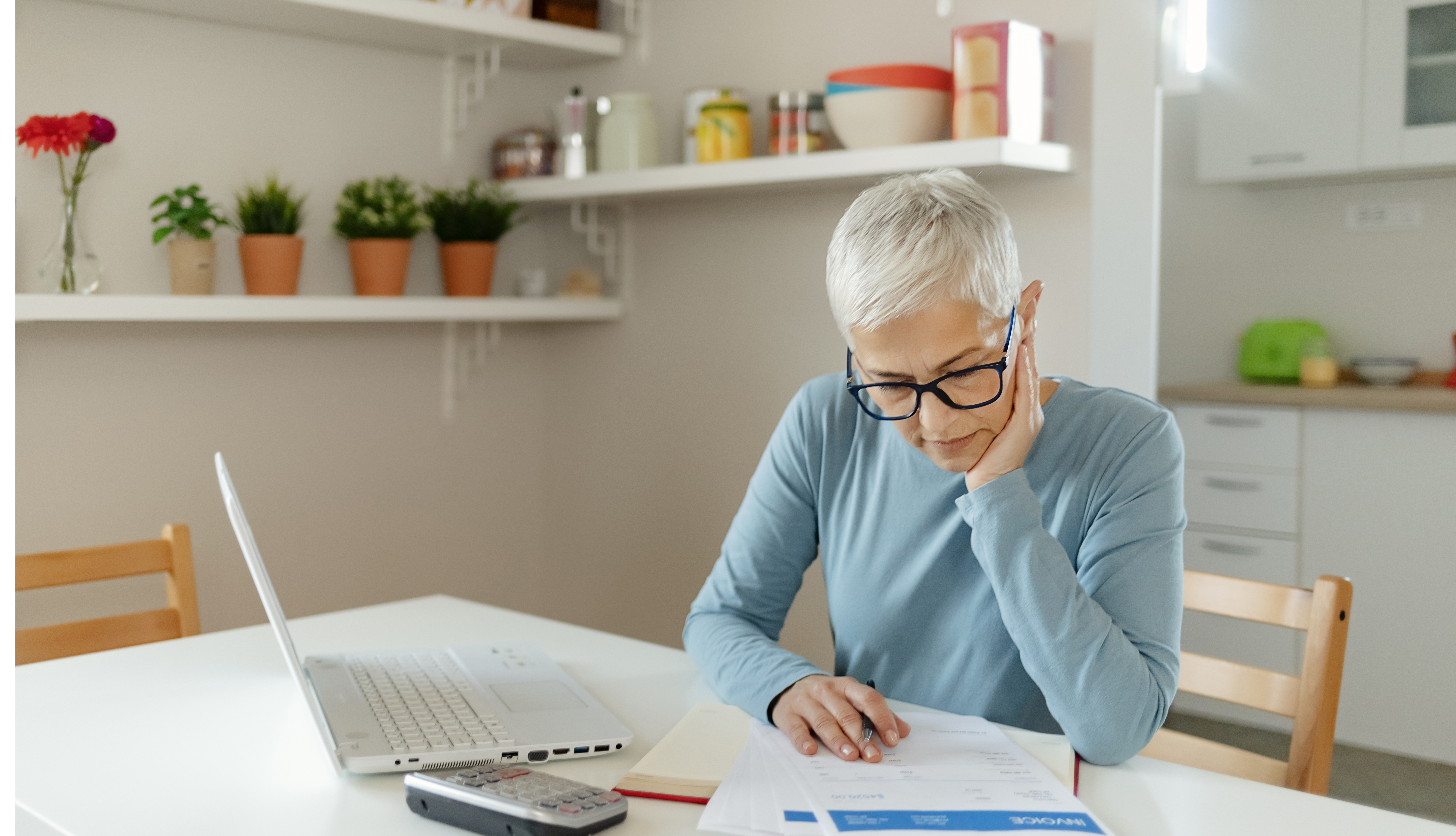 woman looking at forms with laptop and calculator in front of her