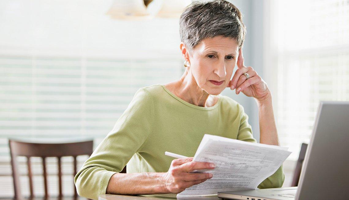 Mujer revisa papeles sentada frente a una computadora