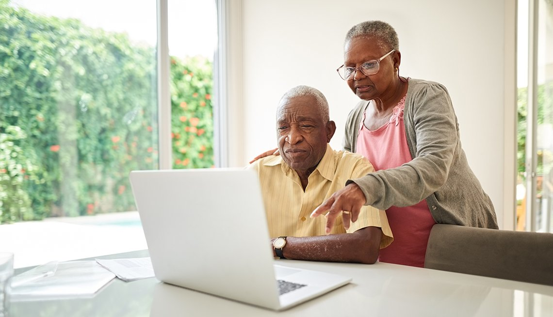 man researching on his laptop with his wife looking over his shoulder and pointing at the screen