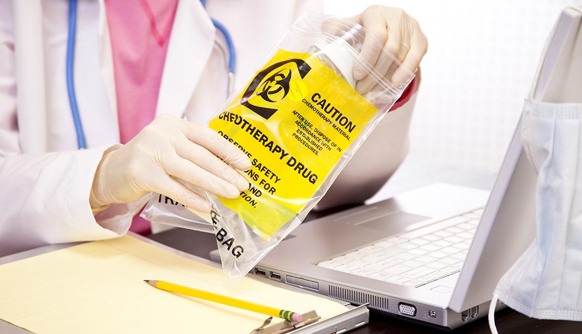 Un médico sostiene un medicamento para quimioterapia