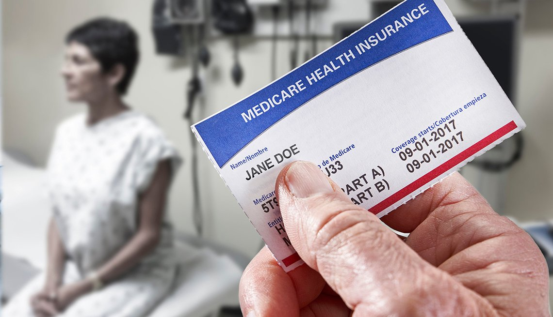 doctor's hand holding a medicare card in the foreground and a patient sitting on an exam table in the background