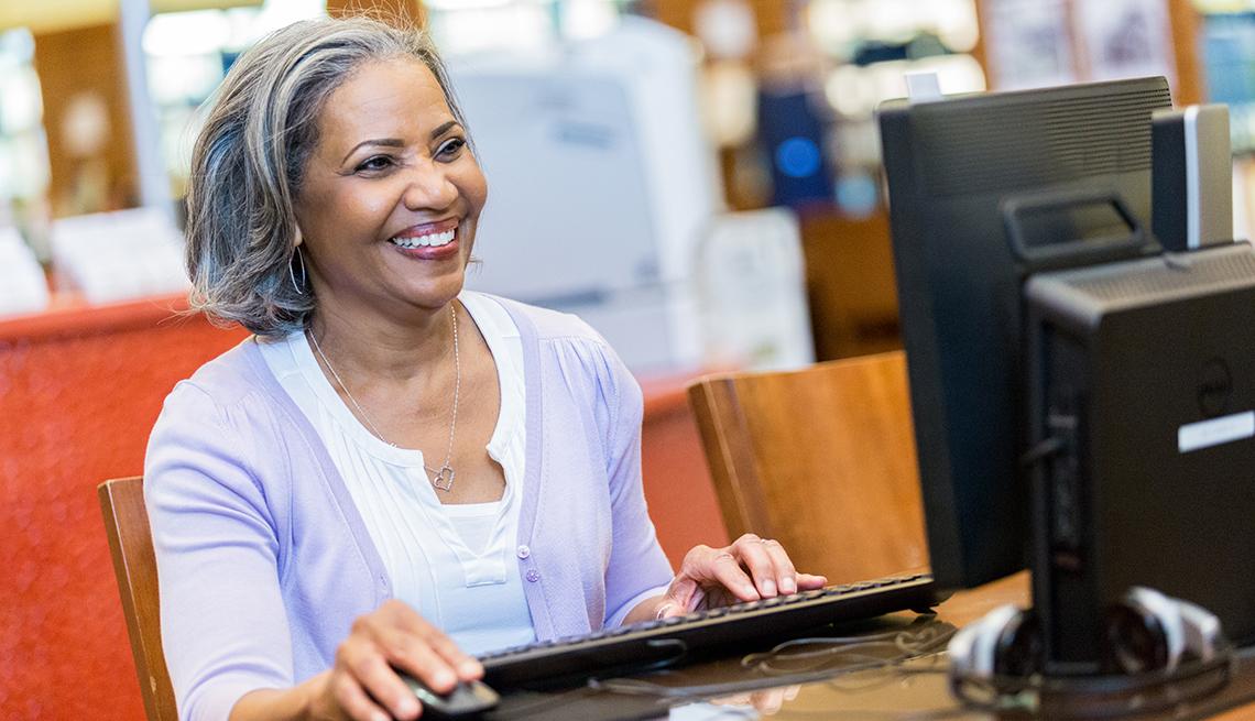 Una mujer utilza una computadora en una biblioteca